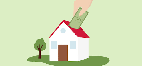 Hand placing cash into the roof of a house.